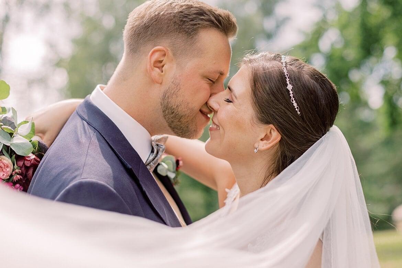 Brautpaar ist kurz davor sich zu küssen, im Vordergrund fliegt der Schleier