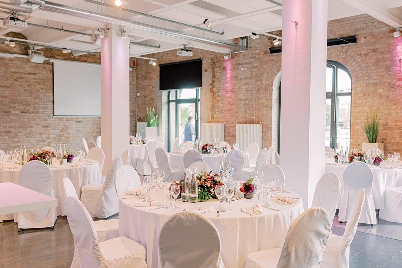Die Feierlocation Spreespeicher von innen mit geschmückten Tischen zur Hochzeit