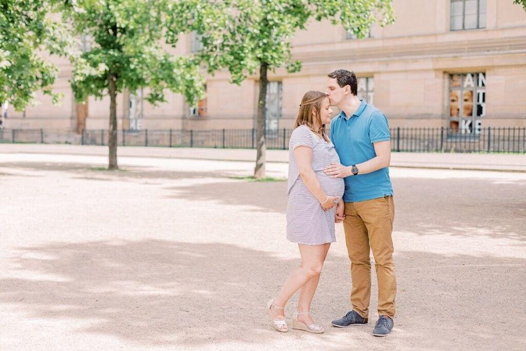 Mann küsst seine schwangere Frau auf die Stirn