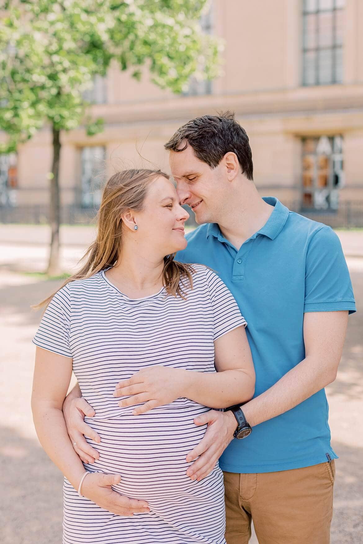 Schwangeres Paar legt Stirn an Stirn