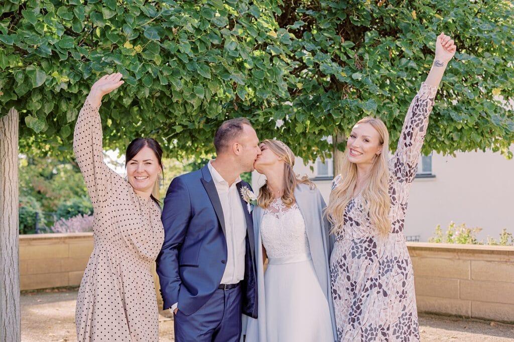 Ein Brautpaar küsst sich und zwei Frauen jubeln
