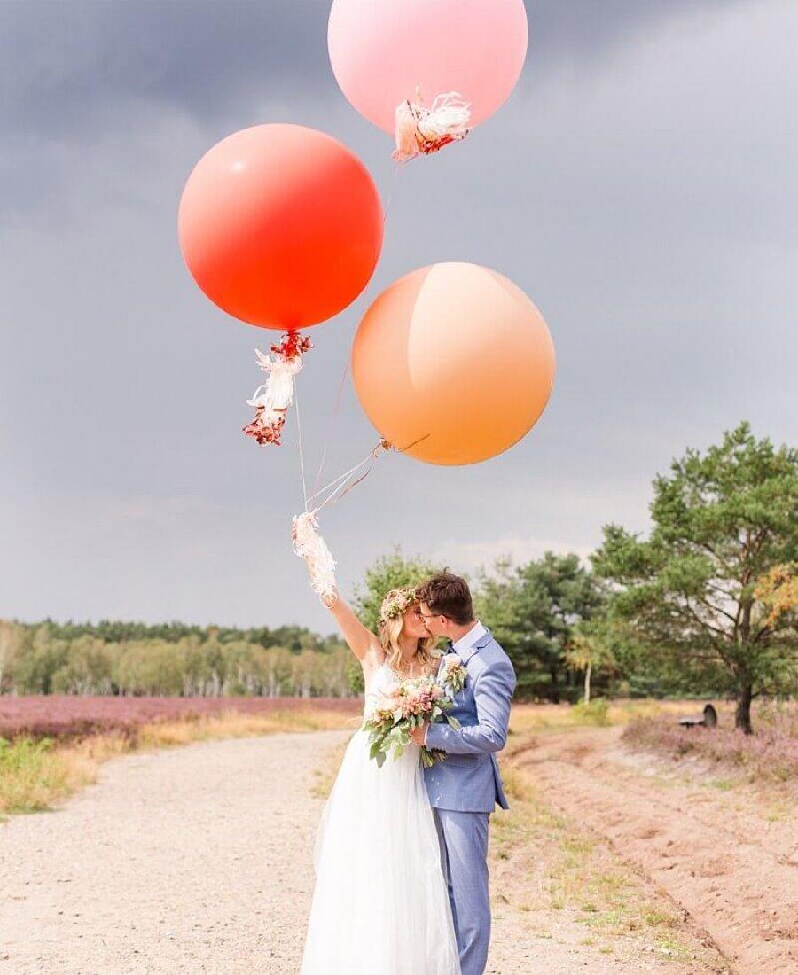 Brautpaar mit drei großen Luftballons in der Lüneburger Heide