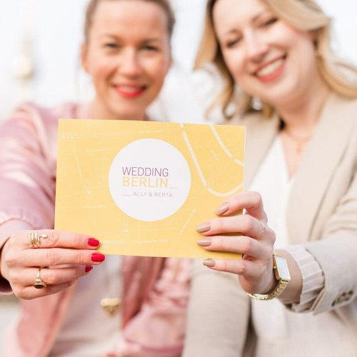 Zwei Frauen halten eine Karte in die Kamera und lächeln