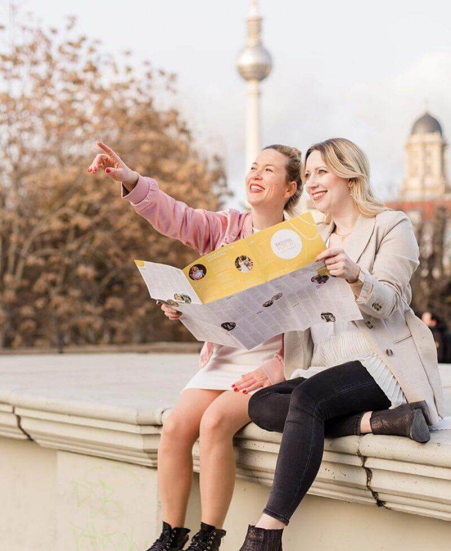 Zwei Frauen sitzen auf einer Mauer vor dem Fernsehturm Berlin, lachen in die Ferne und zeigen auf etwas, dabei halten sie eine Karte fest