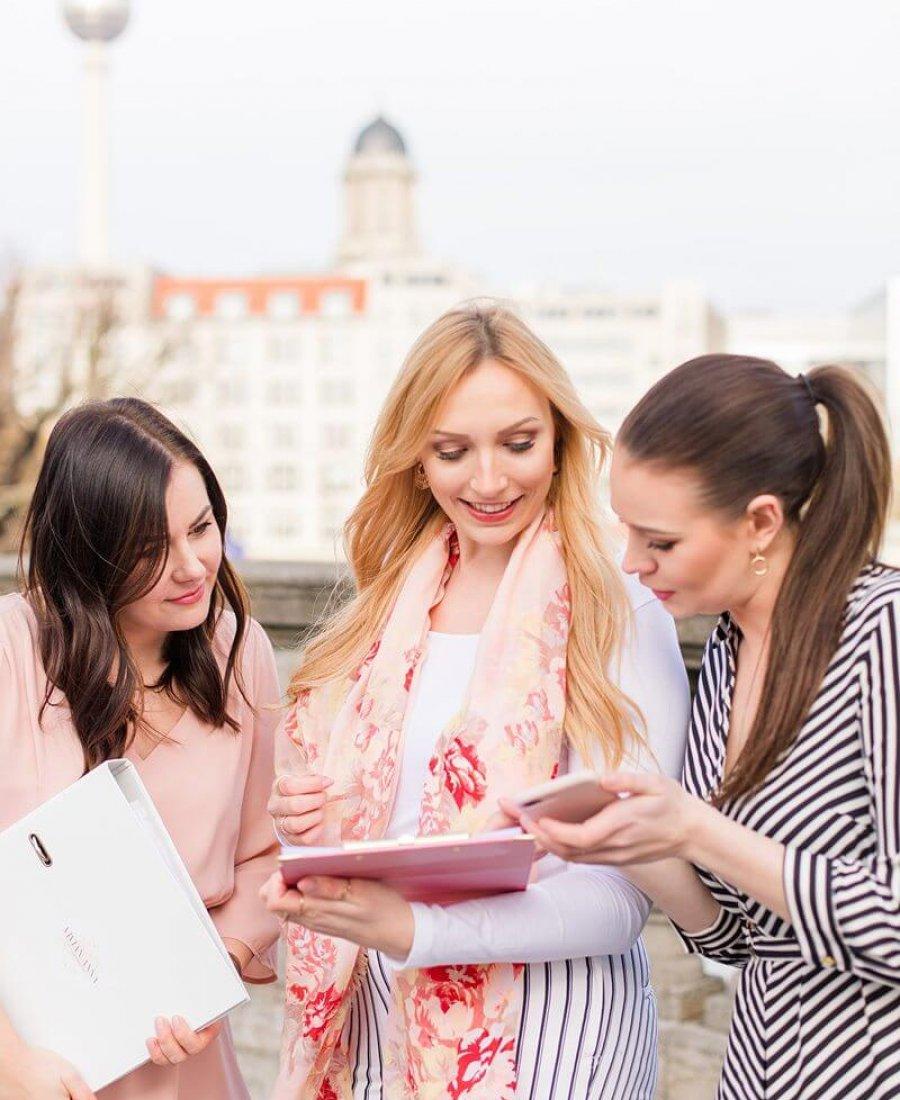 Drei Frauen beugen sich über einen Ordner