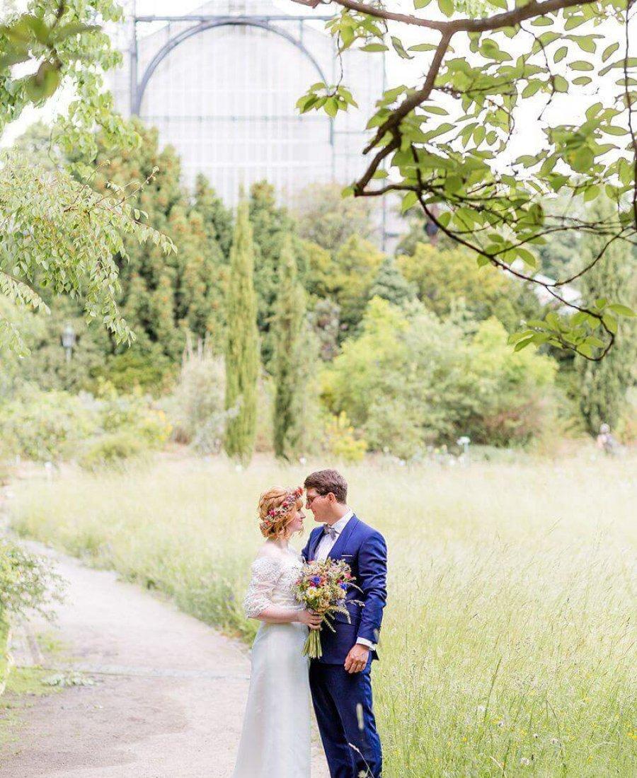 Brautpaar im Park mit Gewächshaus im Hintergrund