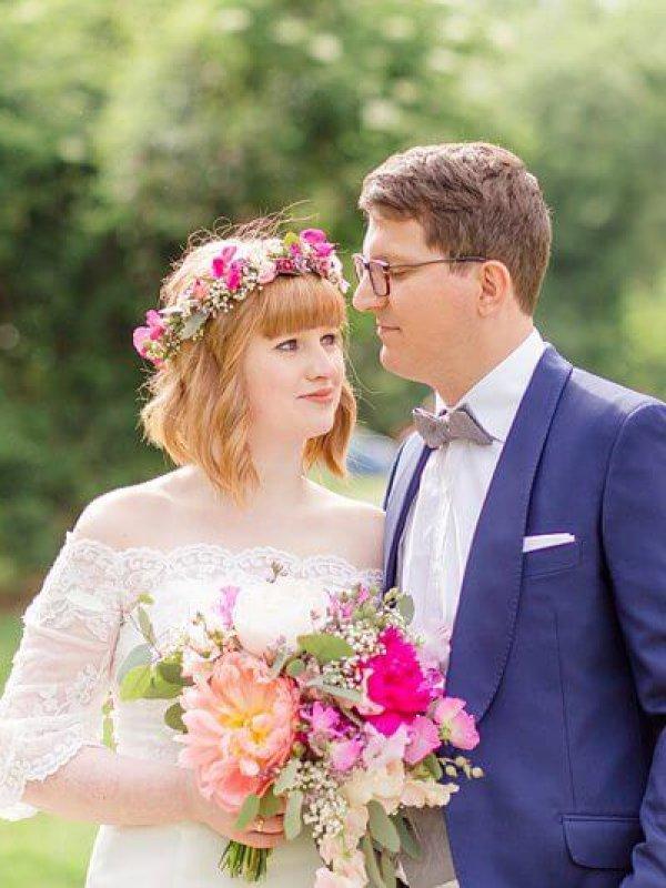 Brautpaar im Grünen mit Blumenkranz und großen pinken Blumen