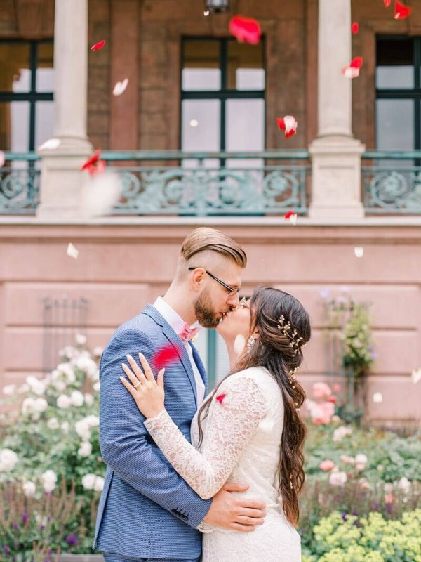 Hochzeitspaar küsst sich unter Blütenregen