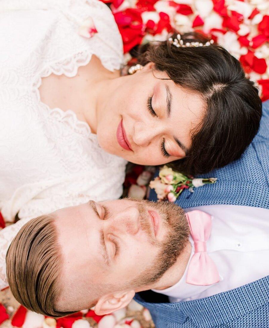 Hochzeitspaar liegt auf Rosenblättern