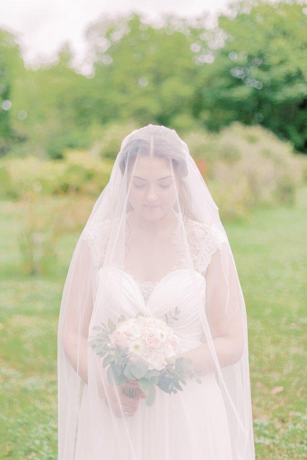Braut unter Schleier im Park