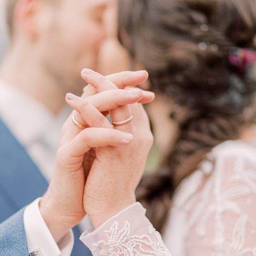 Brautpaar küsst sich im Hintergrund. Im Vordergrund sieht man ihre umschlungenen Hände und Eheringe.
