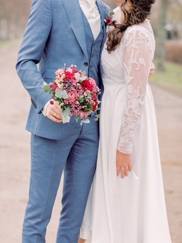 Brautpaar küsst sich, während Bräutigam den Brautstrauß hält