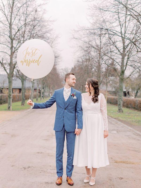 Brautpaar im Winter mit großem Luftballon