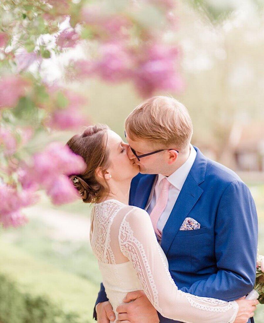 Brautpaar küsst sich unterm Flieder - Hochzeitsfotograf Berlin - Miriam Kaulbarsch