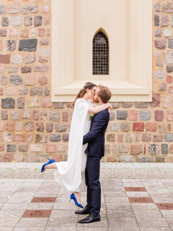 Bräutigam hebt seine Braut in die Luft und sie küssen sich. Braut trägt blaue Manolo Blahnik High Heels.
