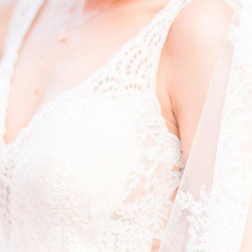 Nahaufnahme einer Braut und ihrem Brautkleid