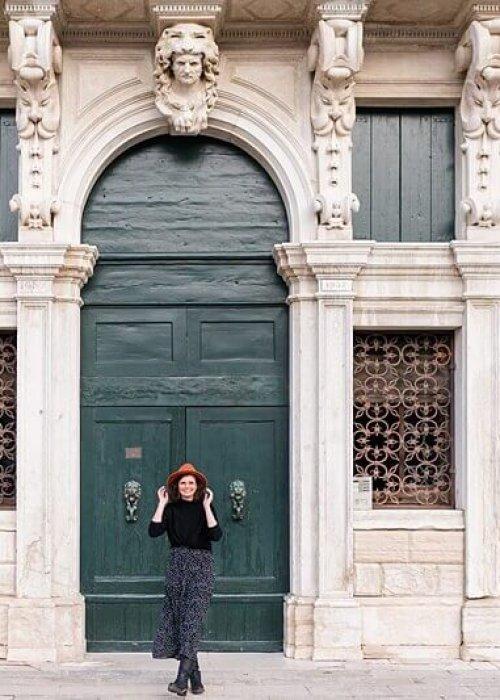 Frau mit Hut und im gepunkteten Kleid vor großem Tor in Venedig