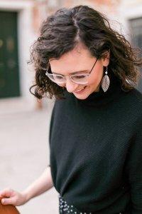 Frau im schwarzen Pullover lacht nach unten
