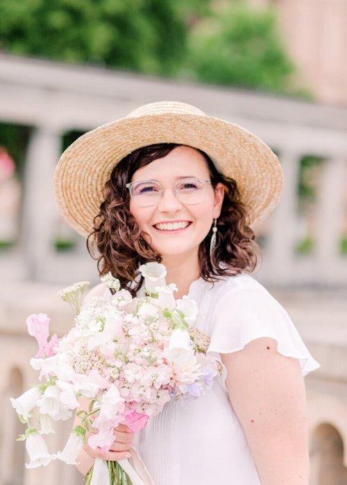 Lachende Frau mit Locken, Strohhut und Blumenstrauß