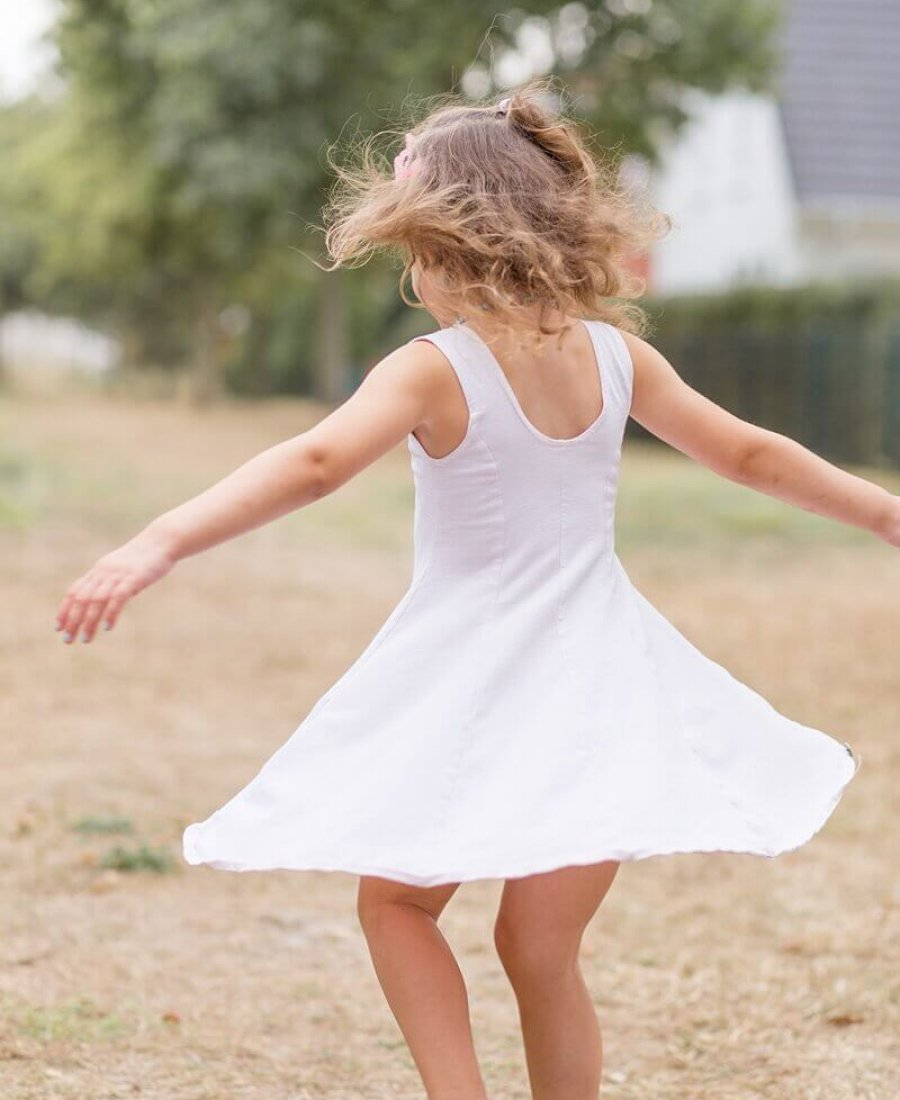 Kind dreht sich mit wehendem Kleid